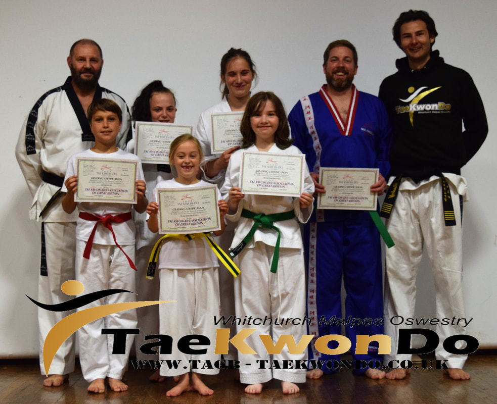 Oswestry Tae Kwon Do students receiving their new belts and certificates from the last colour belt grading.